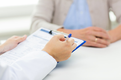 medicine, age, health care and people concept - close up of senior woman and doctor hands with clipboard meeting in medical office